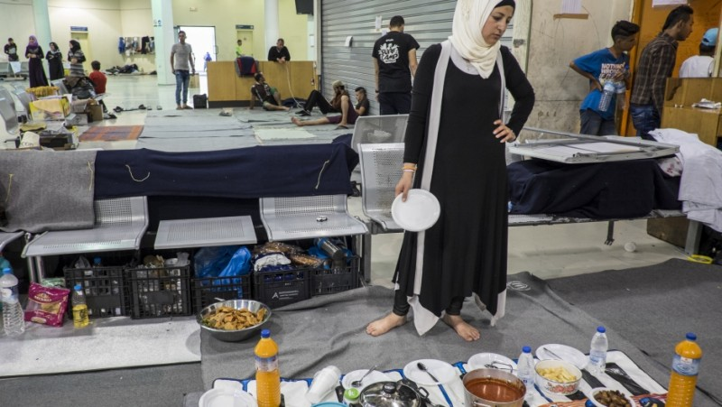 Renna Ramadan prepared an iftar meal for her family, Syrians from Idlib who hoped to reach Northern Europe but instead are living in the passenger waiting area at Piraeus Port Terminal 1 in Athens, Greece. Several hundred refugees and migrants remain at Piraeus, long after Greek authorities vowed to move the people to other camps. Credit: Jodi Hilton/Pulitzer Center