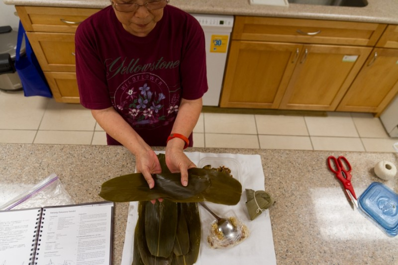 Julie Yu of Milpitas demonstrates how to layer bamboo leaves to make bah tsang, Taiwanese rice dumplings, for the Dragon Boat Festival.