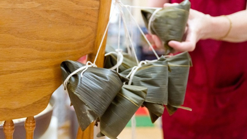 "Eva Chou demonstrates the traditional method of tying Taiwanese bah tsang rice dumplings for the Dragon Boat Festival. She's a bah tsang ""aunty,"" an expert in making the much-loved savory treat — which many American-born Taiwanese don't know how to make. Credit: Grace Hwang Lynch"