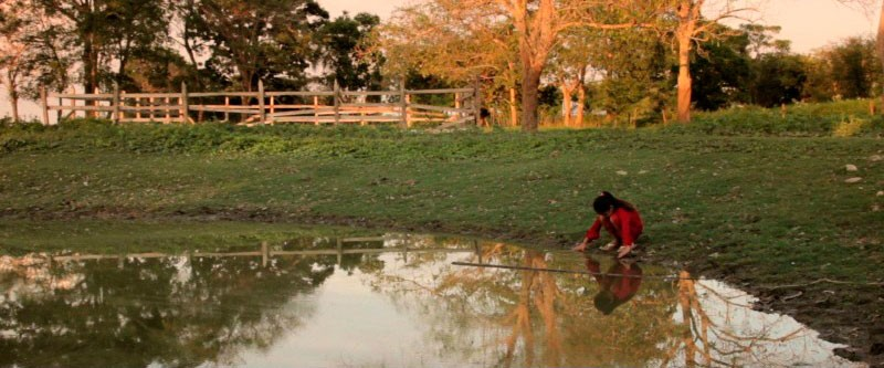 The documentary about the community of El Remolino brings together individual and collective stories on and off screen. This image shows Dana, daughter of Esther, an inhabitant of the town, whilst she looks at her reflection in a lake. Image from the documentary taken from the Facebook page of the producer and published with permission.