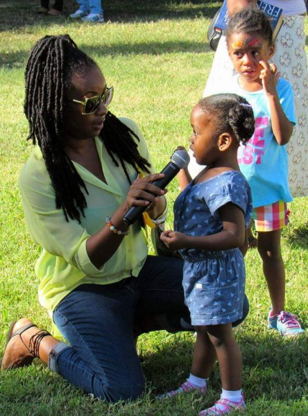 Emprezz Golding talking to a little girl at the Kingston Book Fair in March, 2016. Photo by Emma Lewis, used with permission.