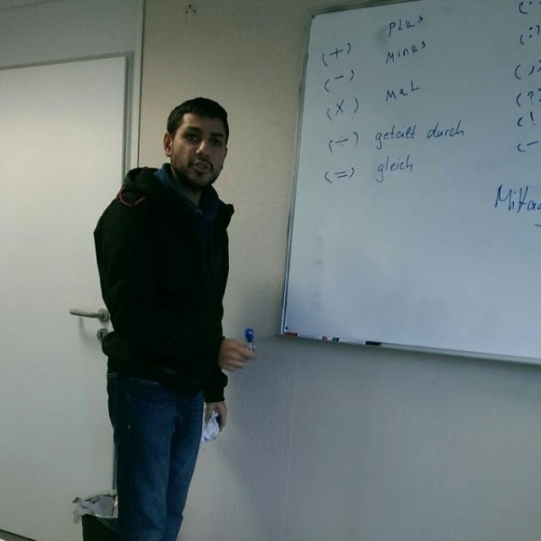 Hassan stands in front of a whiteboard during German language classes in his new hometown. Credit: Hassan Jamous