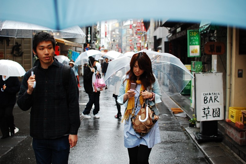 Pedestrians holding umbrellas walk through a city street in the rain