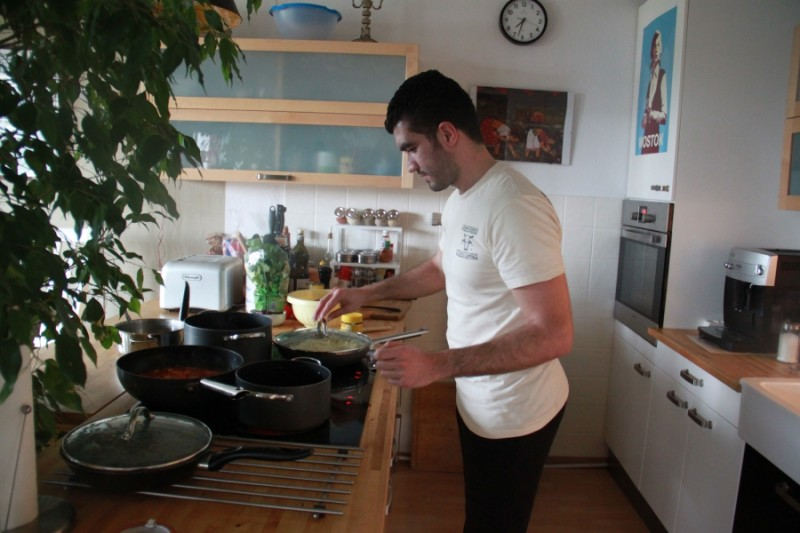 Kinan, a Syrian refugee, prepares a meal for the Jellinek family's Sabbath dinner in Berlin. He says he learned out to cook from youtube videos. Credit: Daniel Estrin. Used with permission