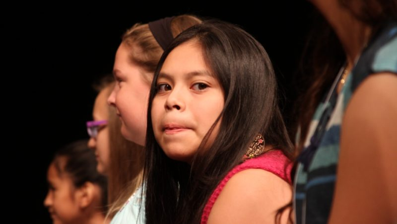 Kiara Rivas-Vasquez, a sixth-grader from Oregon, gives a confident smile to her mother who is watching on from the front row. Credit: Simon Thompson/PRI