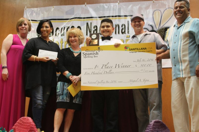 "After winning with the word ""Tahití,"" Jybr Reynoso Hidrogos of Texas is presented with the 2016 National Spanish Championship and $500 in prize money. He is surrounded by organizers of the spelling bee, and the founder and director, David Briseño, who is at the far right. Credit: Simon Thompson/PRI"