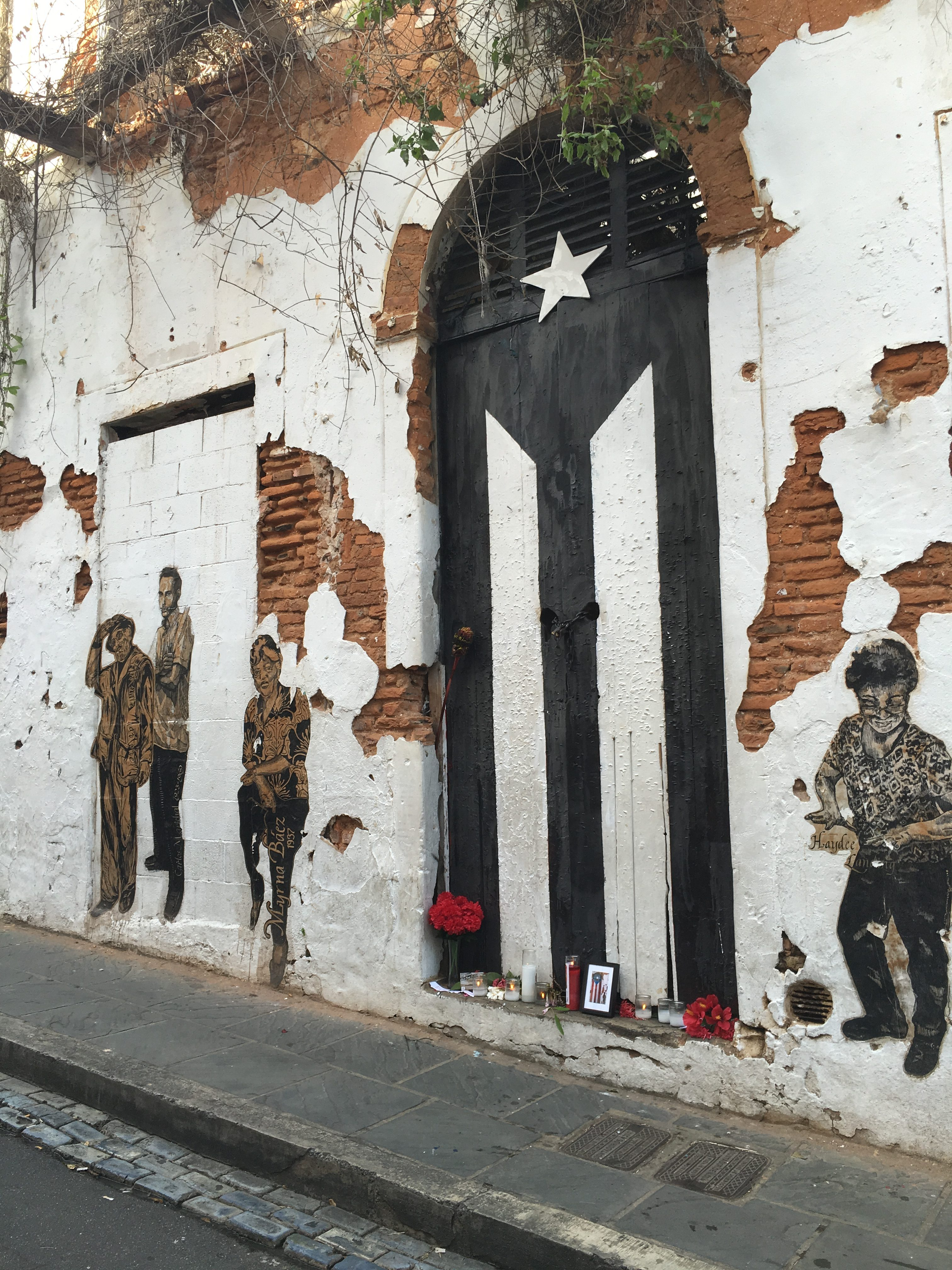 The famous door in Old San Juan now has the Puerto Rican flag painted in black and white, as a sign of mourning and resistance. There is also a small altar. Photo by Marina I. Pineda Shokooh, used with permission.