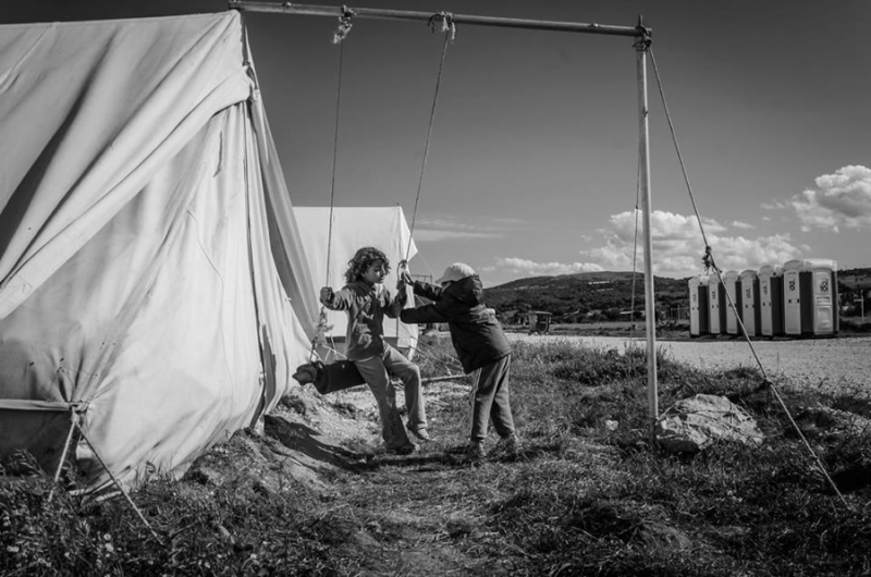 Children play on an improvised swing next to their tent in Katsikas. Photo by Cristina del Campo Martín. Used with permission.