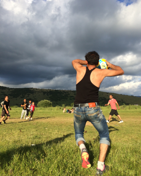 A refugee at Katsikas camp takes a throw-in in a game of football on a nearby field. Photo by author.