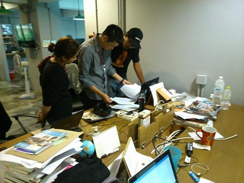 A plainclothes police man searches the desk of a journalist at the Prachatai office. Photo from Prachatai