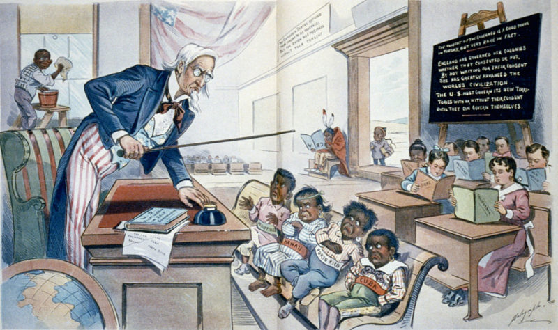 """School Begins. Uncle Sam (to his new class in Civilization): Now, children, you've got to learn these lessons whether you want to or not! But just take a look at the class ahead of you, and remember that, in a little while, you will feel as glad to be here as they are!"" Originally published on p. 8-9 of the January 25, 1899 issue of Puck magazine. By Louis Dalrymple (1866-1905) [Public domain], via Wikimedia Commons."