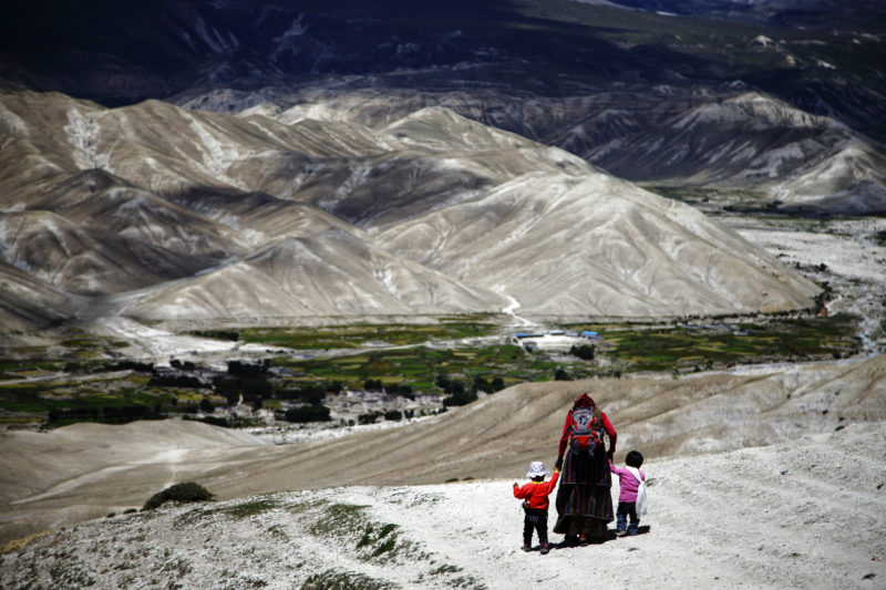 A woman walks with two children as they make their way from Samzong to Lomanthang. Upper Mustang is a remote and isolated region of the Nepalese Himalayas. The Upper Mustang was a restricted demilitarized area until 1992 which makes it one of the most preserved regions in the world, with a majority of the population still speaking traditional Tibetan languages. Tibetan culture has been preserved by the relative isolation of the region from the outside world. 2nd in the category daily life. Image by Gopen Rai. Used with permission.