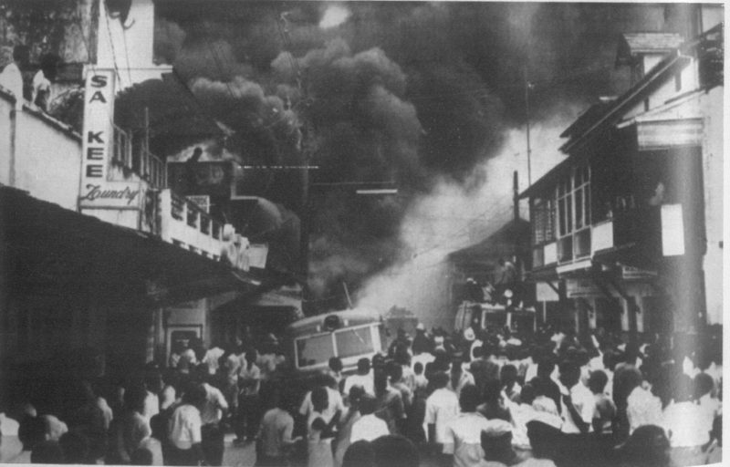 """Trinidad, 1970: Smoke billows as the spirit of Black Power rages in Port of Spain, ushering in a new social paradigm and eroding the old colonial establishment."" Photo from flickr user Angelo Bissessarsingh, used under a CC BY-NC-ND 2.0 license."