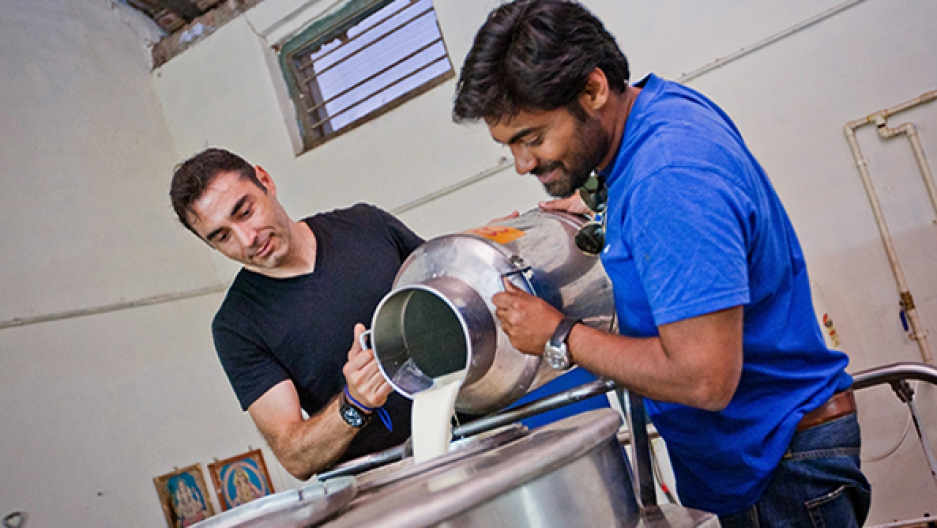 Sorin Grama, left, pours milk into his refrigeration system in India. Credit: Promethean Power Systems