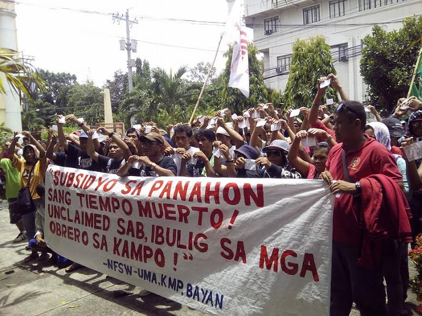 Protesting farmers tear up their pay slips which show the meager salary they receive by working in the sugar plantations. Photo courtesy of UMA Pilipinas