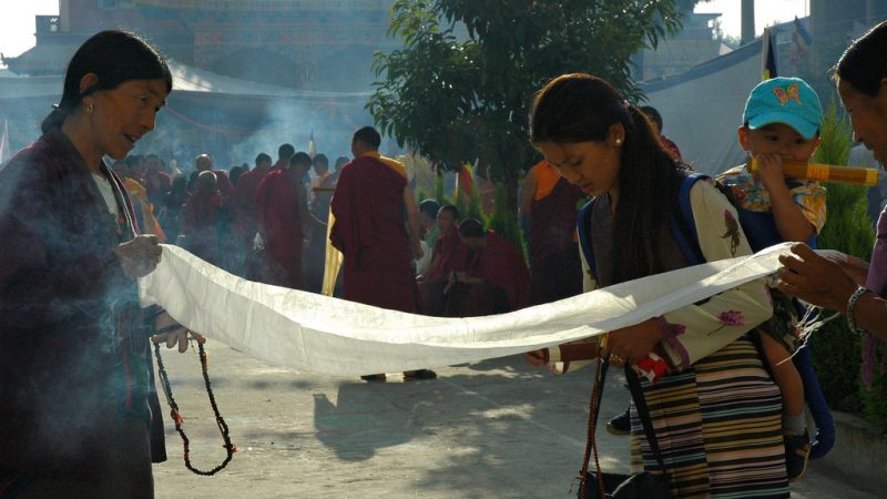 Tibetan ladies chatting while folding a khatag, mother with child, holding incense, a mala, monks, Sakya Lamdre, Tharlam Courtyard, Nepal. Image from Flickr by Wonderlane. CC BY 2.0