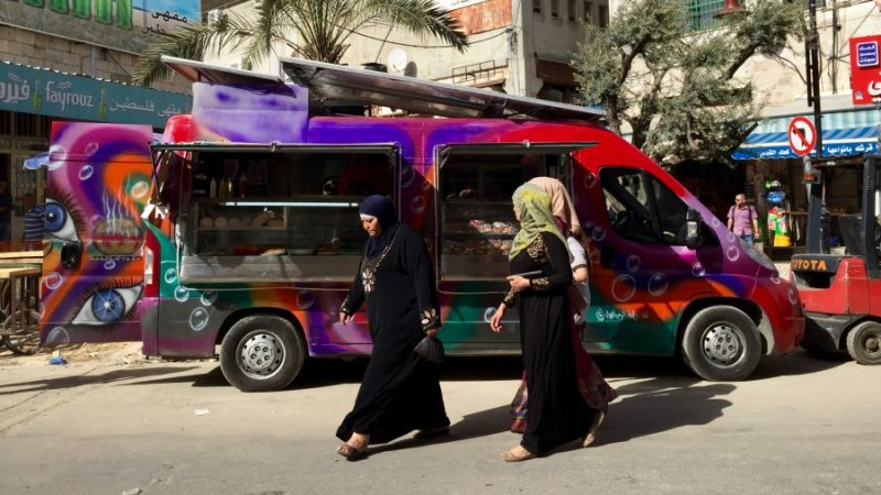 "Palestinian women walk past ""Qitar Ata'am"", which translates into ""the Food Train,"" the first food truck in Ramallah. Credit: Dalia Hatuqa"