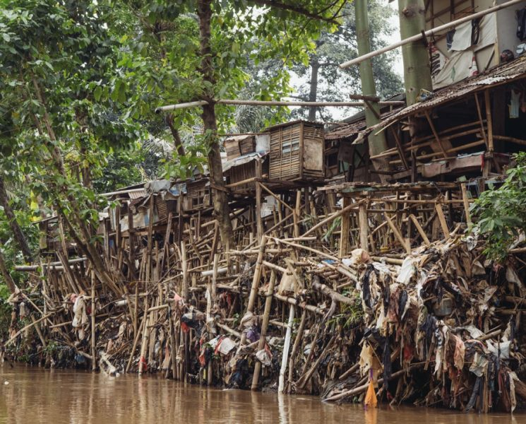 Slums line the Ciliwung river, one of 13 that run through Jakarta. Trash accumlated on the banks shows the high water mark during monsoon season. Credit: Muhammad Fadli/GroundTruth