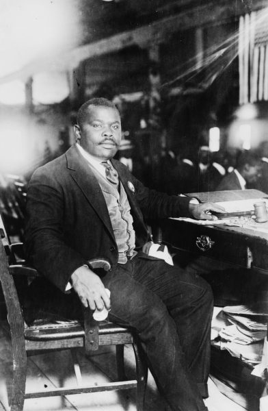 Marcus Garvey, National Hero of Jamaica, seated at his desk, 1924. Public domain. This work is from the George Grantham Bain collection at the Library of Congress. According to the library, there are no known copyright restrictions on the use of this work. Reproduction number LC-USZ61-1854 (b&w film copy neg.). Card #2003653533.