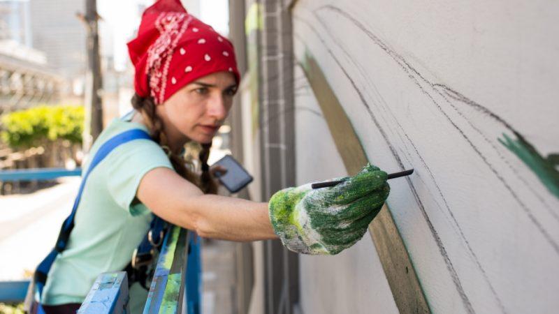 Un'artista di strada dipinge erbacce giganti che rappresentano i margini della societĂ