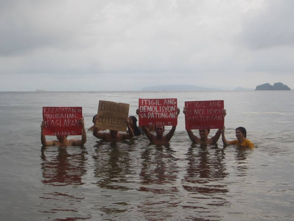 Activists swim and protest while holding placards calling the government to stop the demolition of fishing villages in Patungan Cove. Photo from Pamalakaya Pilipinas.