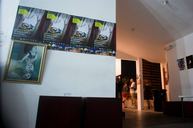 The lobby of The Little Carib Theatre, where a framed portrait of Mc Burnie hangs on the wall. Photo by the trinidad+tobago film festival, used with permission.