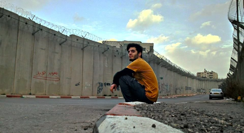 In front of the Apartheid Wall. Uploaded by Ronnie Barkan on Facebook. Source.