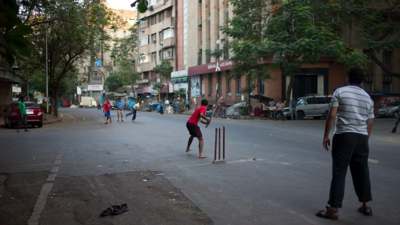 Due to shortage of open space young people resort to play cricket on the streets of Mumbai. Image from Flickr by Mohamed Nanabhay. CC BY 2.0