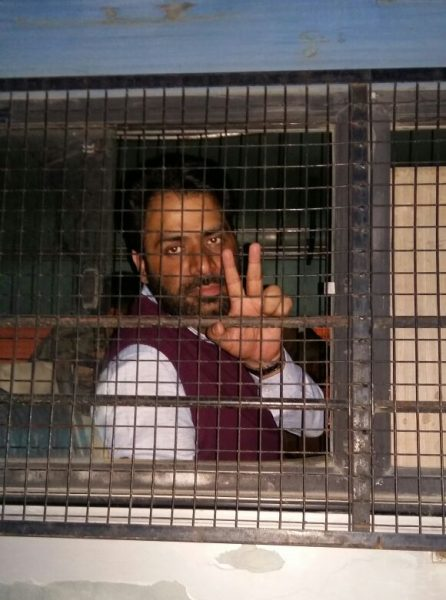 Khurram Parvez shows a victory sign as he is taken to Kot Balawal Jail, Jammu Kashmir. Photo by: Sameena Mir
