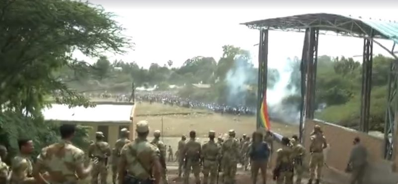 A screenshot from video posted to Facebook by Jawar Mohammed, in which security forces look on as people stampede away. Shots can be heard as smoke rises from the scene.
