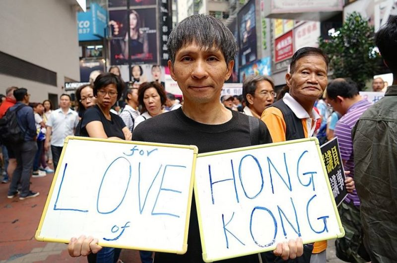 "A demonstrator holds the placard ""I love Hong Kong"" on Sunday rally against Beijing's interpretation of the Basic Law. Photo from inmediahk.net."