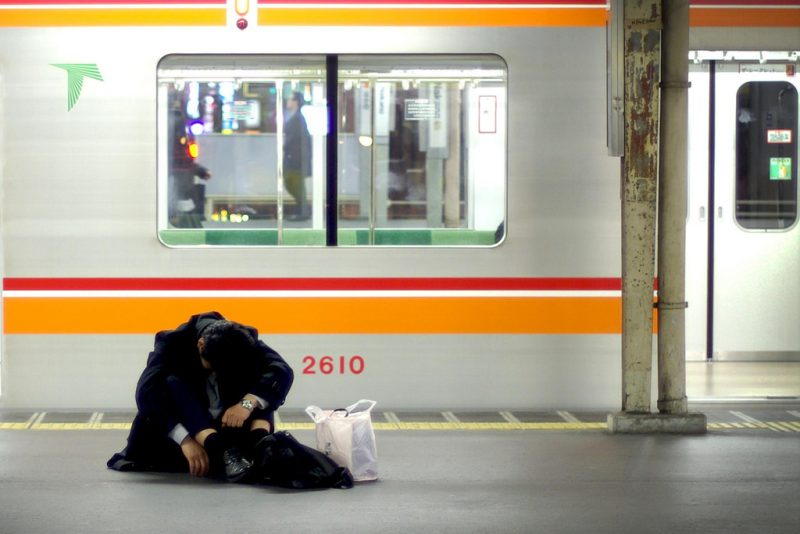 A frazzled salaryman doubled over on the floor of a train platform.