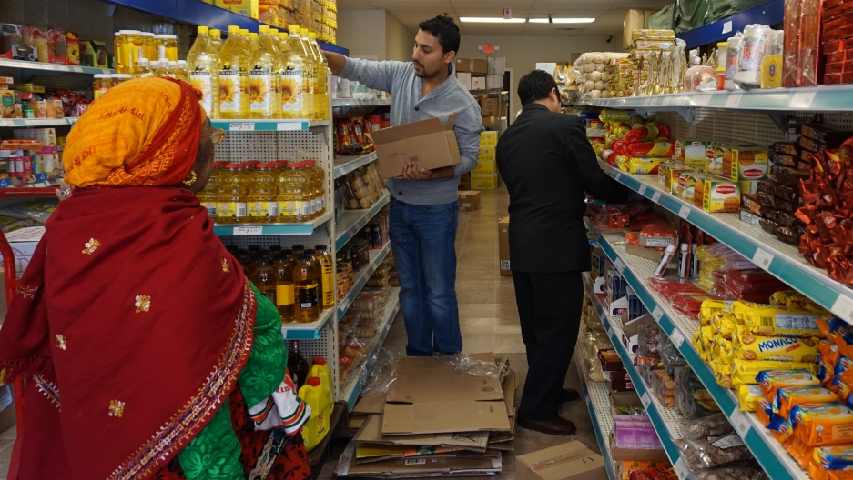 Pradip Upreti, center, stocks shelves in his Erie, Pennsylvania store, UK Supermarket. Credit: Erika Beras
