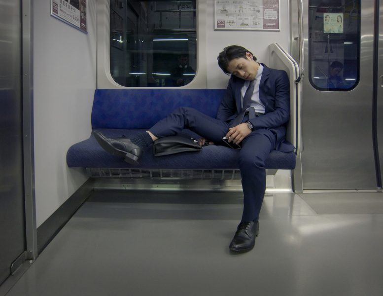 An exhausted businessman sleeping in the train.