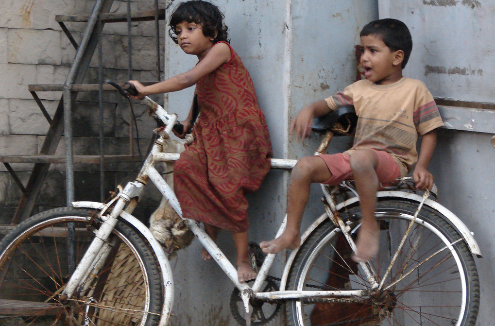 Indian Kids on the street wtih a cycle. Often traditional gender roles are imposed on them (not in this case). Image from Flickr by Harini Calamur . BY-NC-ND 2.0
