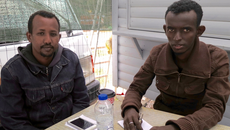 Somali journalists Kamal Hassan and Yassin Abuukar sit at a canteen outside Moria refugee camp in Lesbos, Greece. Credit: Jeanne Carstensen