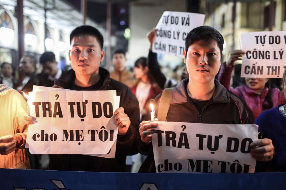 "Cấn Thị Thêu's sons hold signs saying ""Free my mother"" at a candlelight vigil at Thái Hà Parish in Hà Nội, three days before her appeal trial. Image: Facebook/Nguyễn Thịnh"