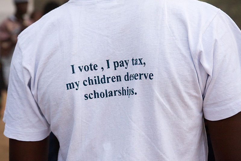 A voter with a t-shirt carrying a political message in the Gambia. Creative Commons photo by Wikipedia user Ikiwaner.