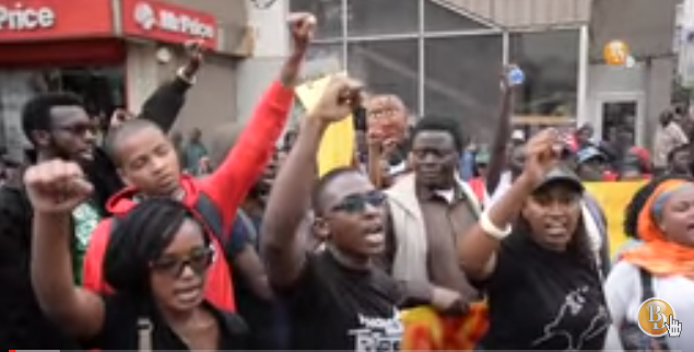 A screenshot of a YouTube video of Kenyans taking part in #TakeBackKenya protest in Nairobi singing with raised fists.