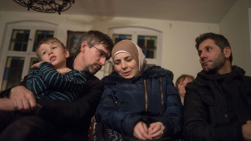 Golzow mayor Frank Schütz, left, leans over to whisper a question to Rasha Haimoud during a holiday concert. She and her husband, Ahmad Haimoud, are refugees who settled in the small former East German town after escaping the war in their native Syria. Credit: Shane McMillan