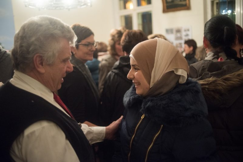A member of Golzow's Protestant Church greets Rasha Haimoud following a holiday concert. Haimoud's family is one of three Syrian refugee families that moved to the village in the last year. The town invited the Muslim families to their annual Christmas concert as a sign of welcome to the rural community on the Polish border. Credit: Shane McMillan