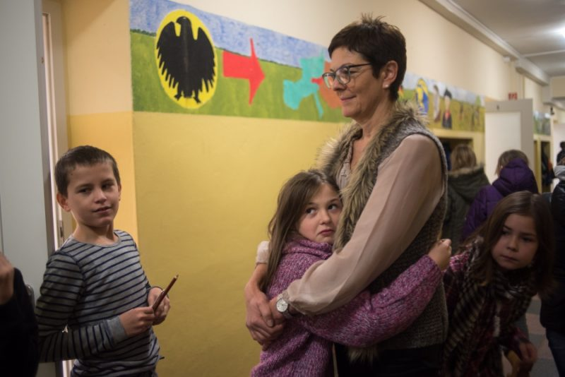 Gabriela Thomas, director of the elementary school in Golzow gives a student a hug between classes in the main hallway. Thomas says that the children of the refugee families are already fitting into her school very well. Credit: Shane McMillan