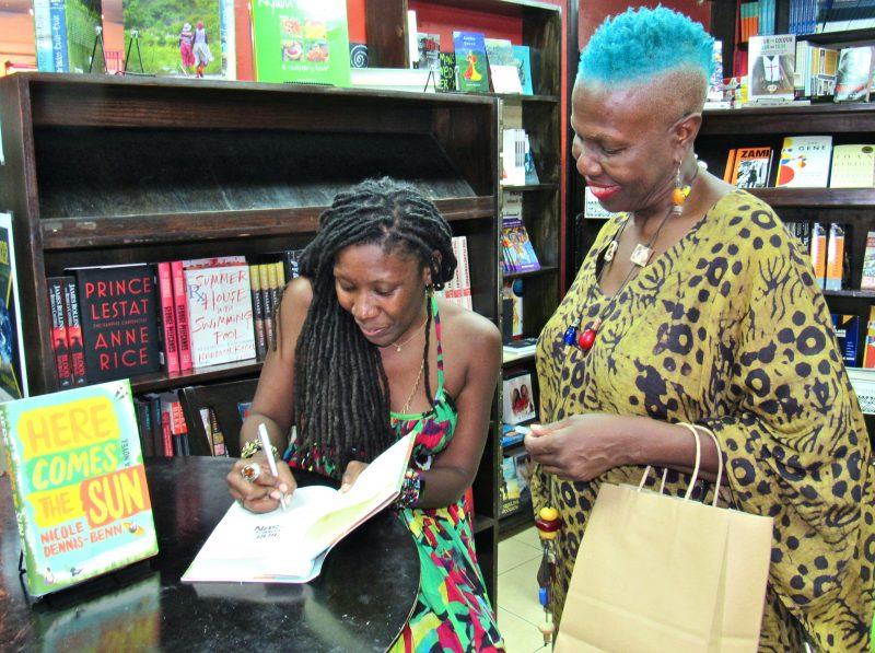 At the book party for her novel 'Here Comes the Sun', Nicole Dennis-Benn signs a copy of her book for Professor Carolyn Cooper. Photo by Emma Lewis, used with permission.