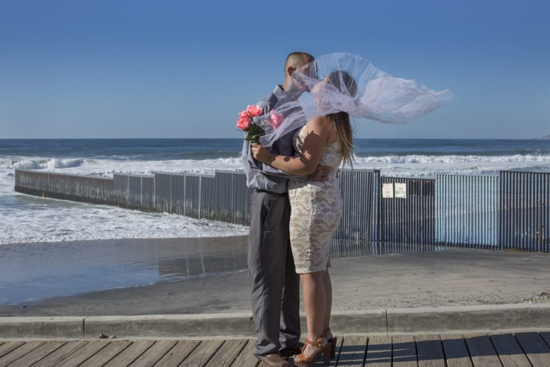 Pastor Jonathan Ibarra i njegova supruga Gladys Lopez na snimanju svadbenih fotografija ispred ograde na granici SAD-Meksika u Playas de Tijuana, Meksiko, 12. decembar 2015. Granica je simbolično mesto za Ibarra i Lopez, i koji su oboje odrasli u Kaliforniji, ali sada žive u Tijuani, odvojeni od svoje porodice. Ibarra je deportovan, a Lopez nema dokumente koji su joj potrebni da dobije stalni boravak u SAD. Tri puta je pokušala da pređe, ali su je uhKoristi se uz dozvoluvatili graničari i vratili je u Meksiko. Fotografija: Griselda San Martin. Used with permission.