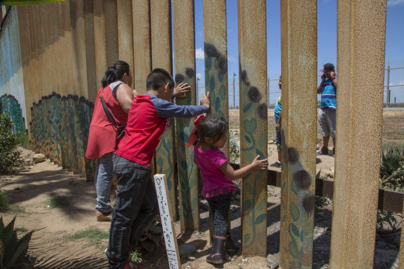 カルメン・モラレスが孫のクリスティアン(8歳)、ソフィア(4歳)とともに、初めて義理の娘と孫のジェシー(15歳)、クリスタル(11歳)に対面する様子。義理の娘たちはカリフォルニア州、サンバーナーディーノに住んでいる。鉄の棒は抱きしめられるぐらい十分に離れて立っているが、アメリカ側から近寄ることは許されていないため、抱きしめることはできない。写真提供:グリセルダ・サン・マルティン(掲載許諾済)