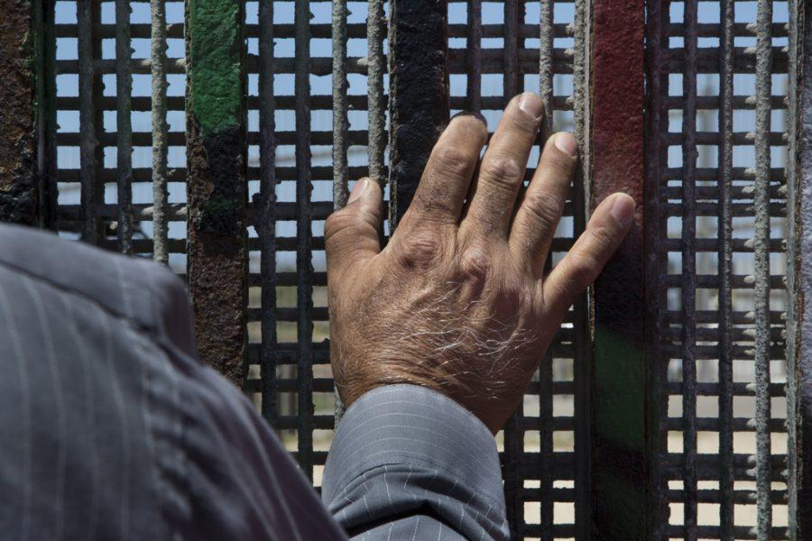 ティフアナにあるボーダー・チャーチの週次集会のため、フレンドシップパークの国境のフェンスに立つ、メソジスト教会のギエルモ・ナバレテ牧師。壁の両側で英語とスペイン語の説教が同時に行われる。2016年5月22日撮影。写真提供:グリセルダ・サン・マルティン(掲載許諾済)