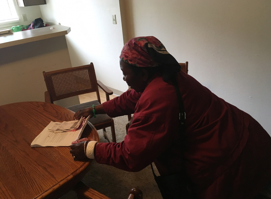 Mme Yulina Bilombele, 80 ans, rassemble son avis d'éviction et ses reçus du loyer pour M. Floribert Mubalama pour qu'il les lui traduise parce qu'elle ne parle pas anglais. Les deux sont des réfugiés de la République démocratique du Congo vivant dans la zone métropolitaine de Seattle. Crédit: Isabel Vázquez / NextGenRadio