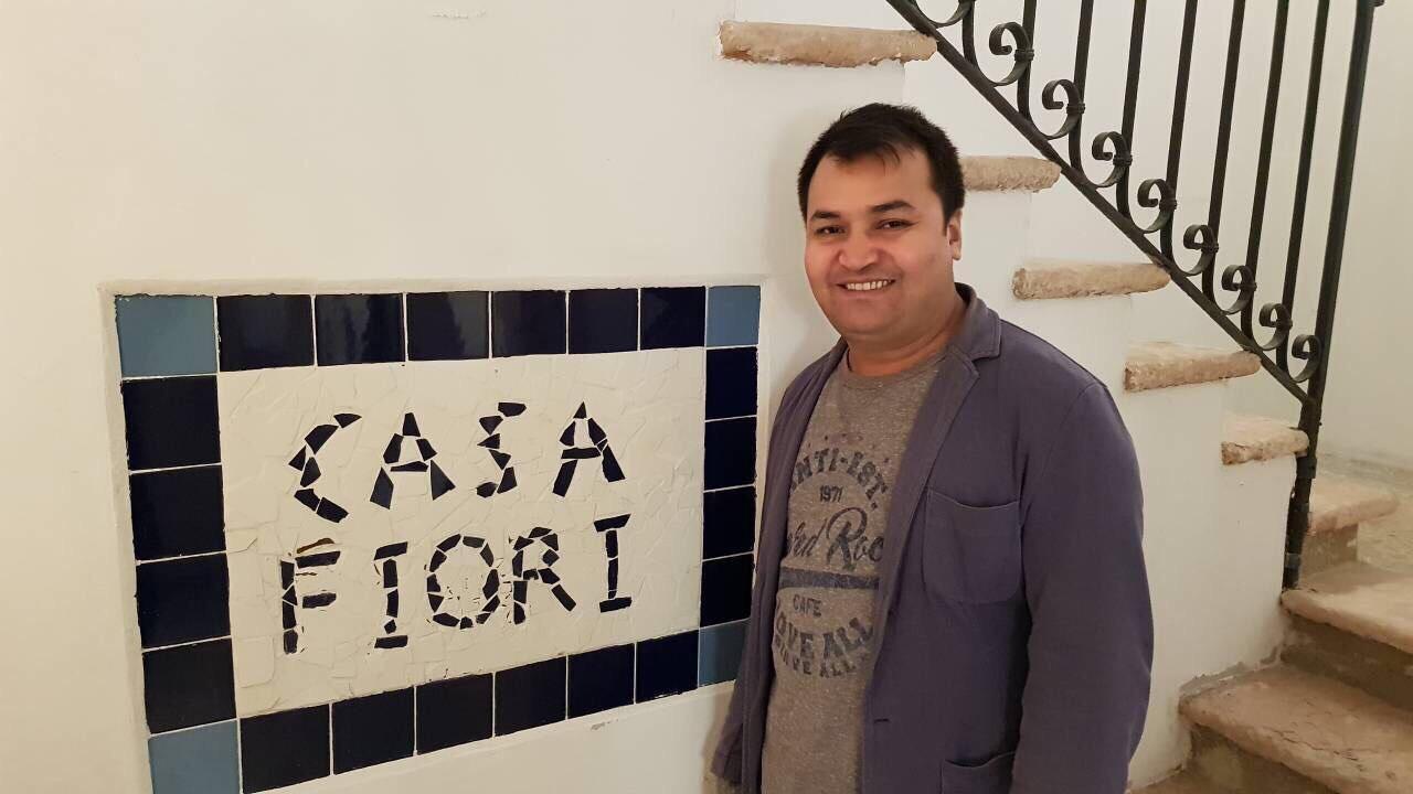 """Asharaf Barati devant """"Casa Fiori"""", l'une des auberges qu'il possède à Venise. Photo par Basir Ahang. Utilisé avec permission."""