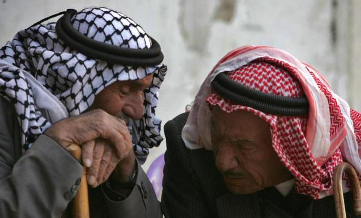 "Man wearing the Kofeyeh (traditional Palestinian head accessory) talking to a man wearing Shmagh (traditional Jordanian head accessory). Photo released to public domain, Source: <a href=""https://www.garaanews.com/%D9%85%D8%B9%D8%A7%D8%B1%<a href=""https://www.garaanews.com/%D9%85%D8%B9%D8%A7%D8%B1%D9%8A%D9%81-%D8%AD%D9%84-%D9%81%D9%8A%D8%AF%D8%B1%D8%A7%D9%84%D9%8A-%D8%A7%D8%B1%D8%AF%D9%86%D9%8A-%E2%80%93-%D9%81%D9%84%D8%B3%D8%B7%D9%8A%D9%86%D9%8A"">Garaa News</a>."