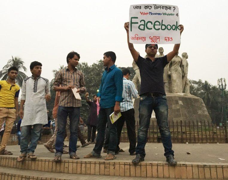 """Um protestante na Universidade de Dhaka no Bangladesh, durante o apagão das redes sociais de 2015. O cartaz diz """"Quantas mais desculpas? Abram o Viber, o Messenger, o WhatsApp e o Facebook JÁ."""" Foto de Zaid Islam, usada com permissão."""